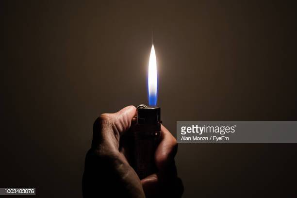 close-up of hand holding lit cigarette lighter in darkroom - cigarette lighter stock pictures, royalty-free photos & images