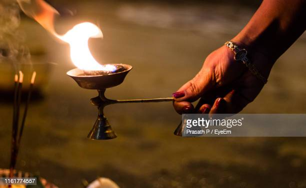 close-up of hand holding lit diya in temple - ceremony stock pictures, royalty-free photos & images