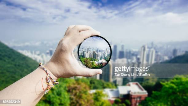 Close-Up Of Hand Holding Magnifying Glass Against Cityscape