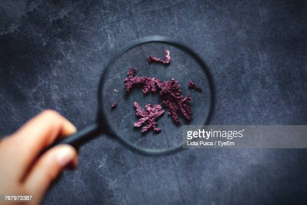 Close-Up Of Hand Holding Magnifying Glass Over Wine Sediment