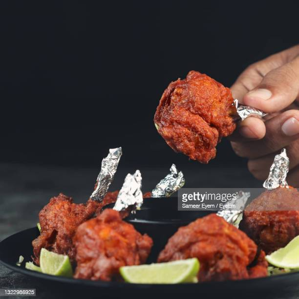 close-up of hand holding meat - tikka masala stock pictures, royalty-free photos & images