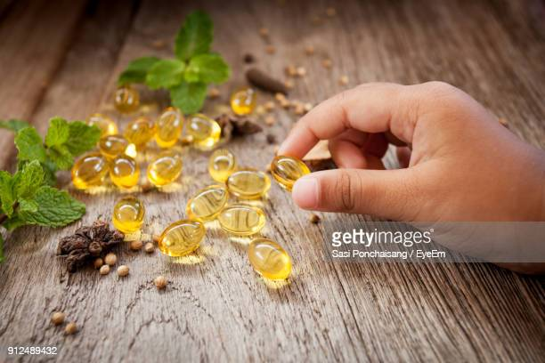 close-up of hand holding medicine - fatty acid stock pictures, royalty-free photos & images