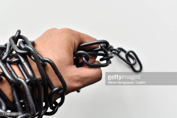 close-up of hand holding metal chain against white background - wimol wongsawat stock photos and pictures