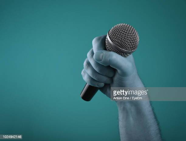 close-up of hand holding microphone against blue background - eine person stock pictures, royalty-free photos & images