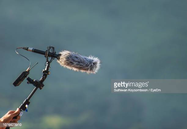 close-up of hand holding microphone against sky - sound recording equipment stock pictures, royalty-free photos & images