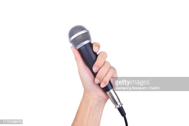 close-up of hand holding microphone against white background - microphone stock pictures, royalty-free photos & images