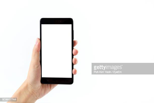 close-up of hand holding mobile phone against white background - cogiendo fotografías e imágenes de stock
