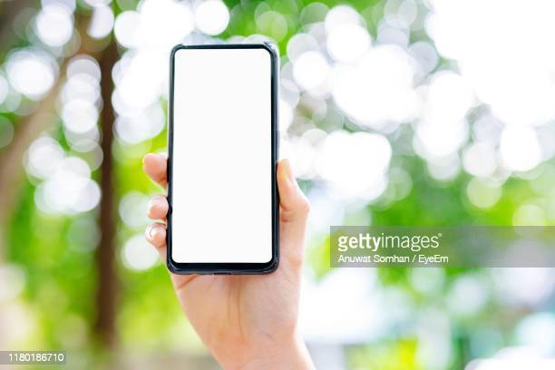 close-up of hand holding mobile phone - anuwat somhan stock photos and pictures