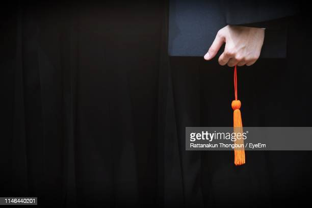 close-up of hand holding mortarboard against black background - graduation background stock pictures, royalty-free photos & images
