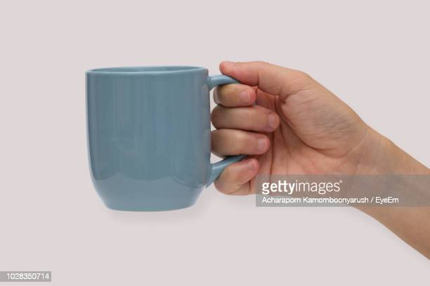 close-up of hand holding mug over white background - mug stock pictures, royalty-free photos & images