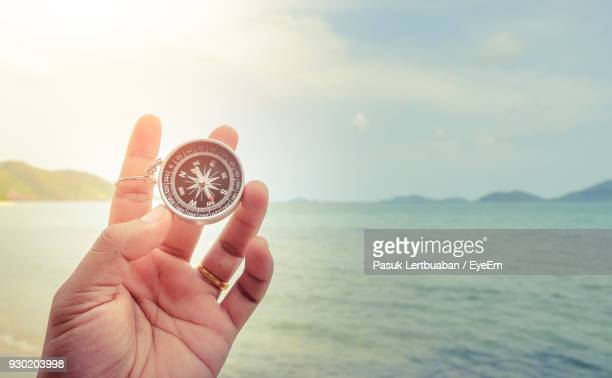 close-up of hand holding navigational compass against sea - compass stock pictures, royalty-free photos & images