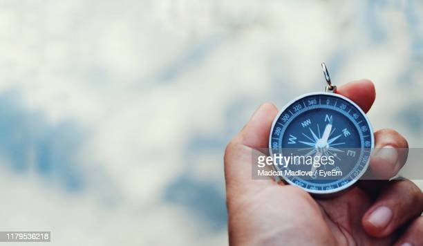 close-up of hand holding navigational compass outdoors - compass stock pictures, royalty-free photos & images