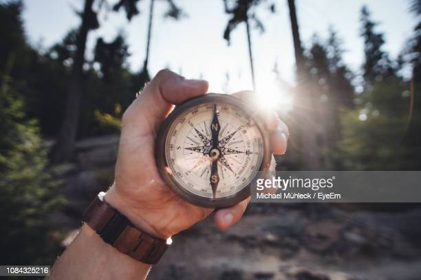 close-up of hand holding navigational compass - compass stock pictures, royalty-free photos & images