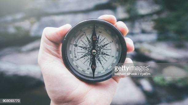 close-up of hand holding navigational compass - guidance stock pictures, royalty-free photos & images