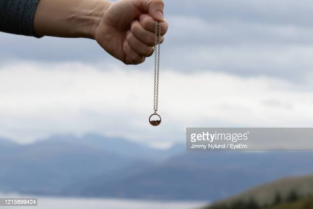 close-up of hand holding necklace against cloudy sky - ペンダント ストックフォトと画像