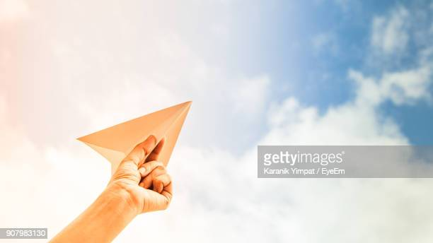 close-up of hand holding paper airplane against sky - gaivota - fotografias e filmes do acervo