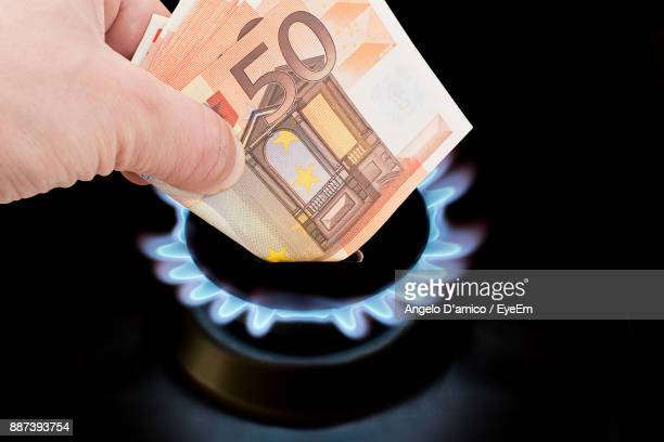 Close-Up Of Hand Holding Paper Currency Over Gas Stove Burner