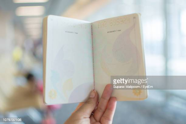 close-up of hand holding passport - passeport photos et images de collection