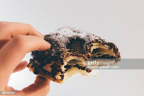 Close-Up Of Hand Holding Pastry Against White Background
