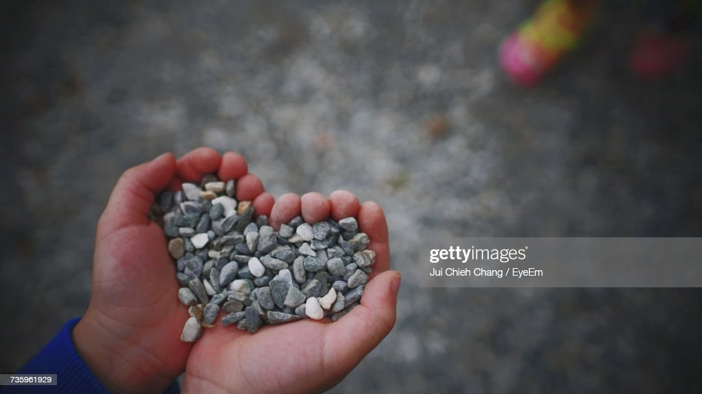 Close-Up Of Hand Holding Pebbles : Stock Photo