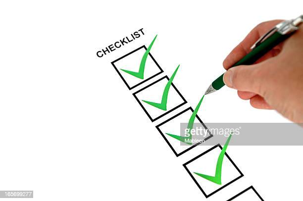 Close-up of hand holding pen making marks on a checklist