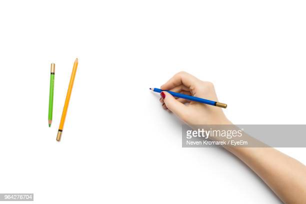 close-up of hand holding pencil against white background - color pencil stock pictures, royalty-free photos & images