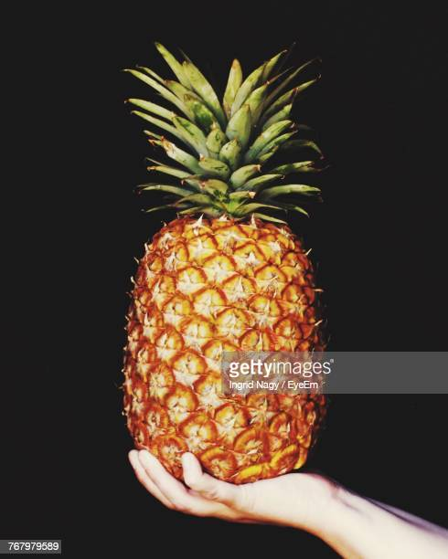 Close-Up Of Hand Holding Pineapple Against Black Background
