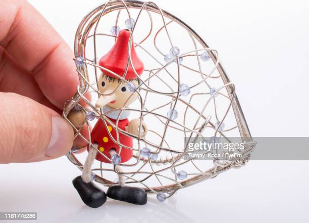 close-up of hand holding pinocchio in trapped metallic toy against white background - caught cheating stock pictures, royalty-free photos & images