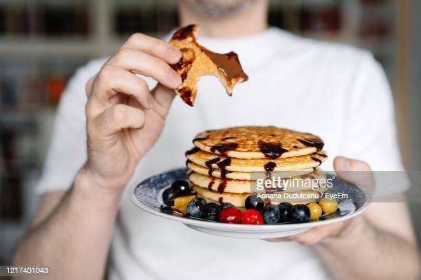 close-up of hand holding plate with pancakes - pancakes stock pictures, royalty-free photos & images
