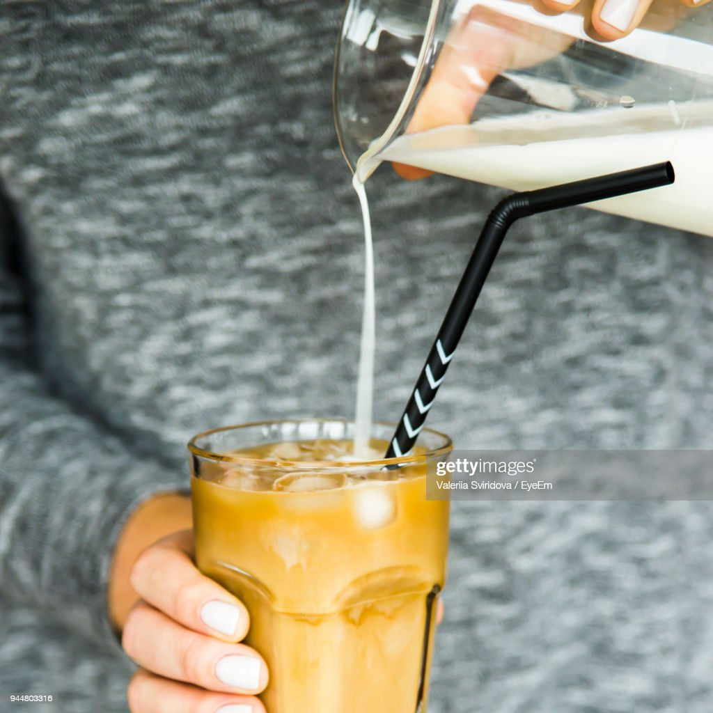 Close-Up Of Hand Holding Pouring Milk In Cold Coffee On Table : Stock Photo