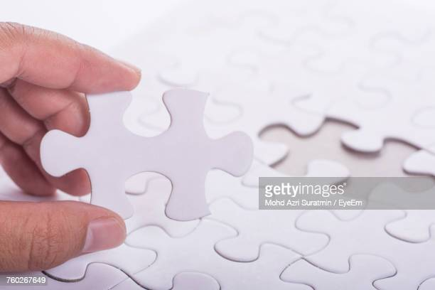Close-Up Of Hand Holding Puzzle