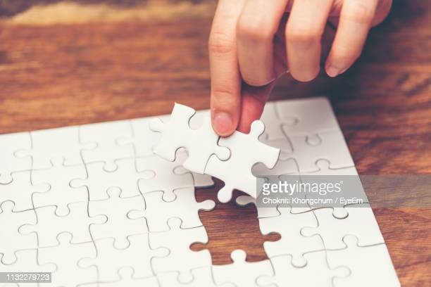close-up of hand holding puzzle piece - inserting stock pictures, royalty-free photos & images