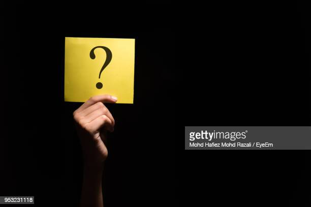 close-up of hand holding question mark on yellow paper against black background - mistério - fotografias e filmes do acervo