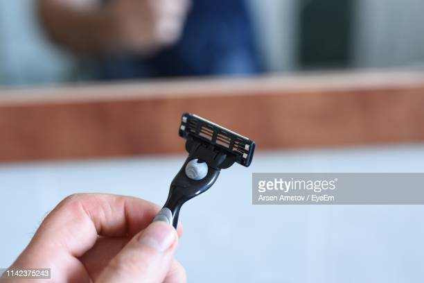 close-up of hand holding razor - razor stock photos and pictures
