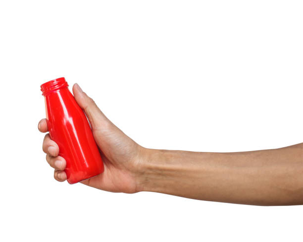 close-up of hand holding red bottle over white background - human hand stock pictures, royalty-free photos & images
