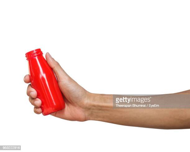 Close-Up Of Hand Holding Red Bottle Over White Background