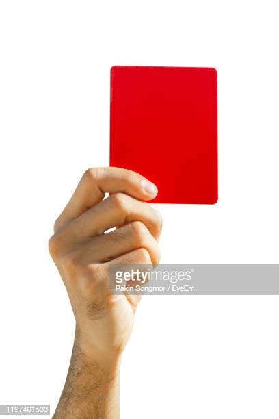 close-up of hand holding red card against white background - スポーツ レッドカード ストックフォトと画像