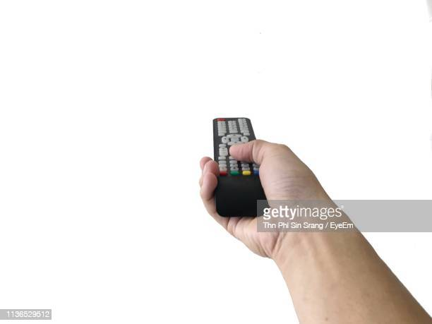 close-up of hand holding remote control against white background - remote control stock pictures, royalty-free photos & images