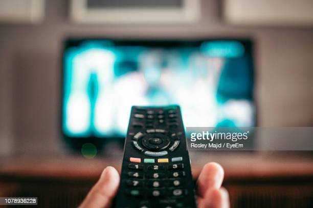 close-up of hand holding remote control at home - remote control stock pictures, royalty-free photos & images