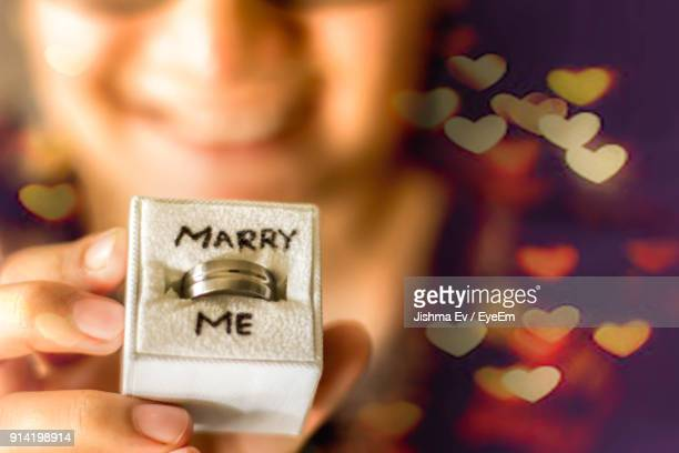 close-up of hand holding ring with text on box - engagement ring box stock photos and pictures