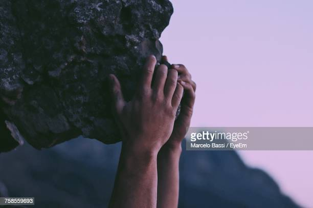 Close-Up Of Hand Holding Rock Against Sky