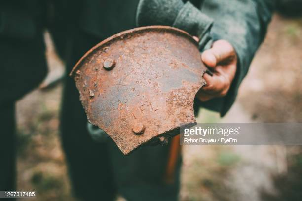 close-up of hand holding rusty metal part - world war i stock pictures, royalty-free photos & images