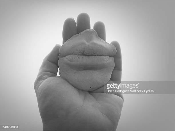 Close-Up Of Hand Holding Sculpted Human Mouth