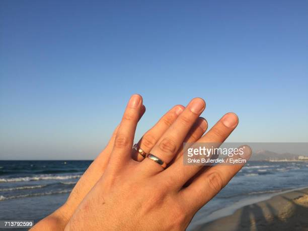 Close-Up Of Hand Holding Sea Against Clear Sky