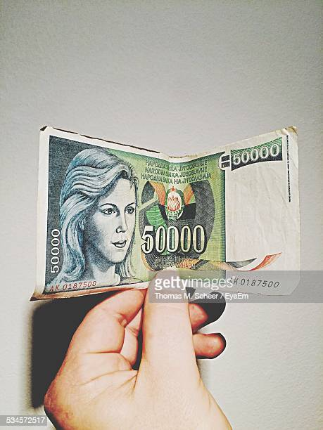 Close-Up Of Hand Holding Serbian Dinars Over White Background