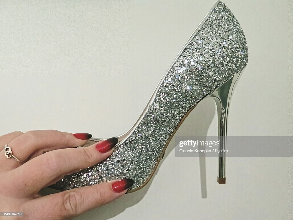 Close-Up Of Hand Holding Shiny High Heel Over White Background : Stock Photo