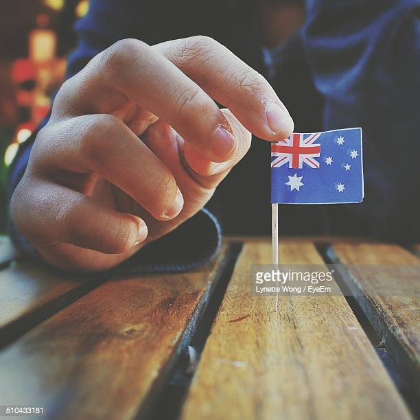 close-up of hand holding small australian flag at wooden table - australian flag stock pictures, royalty-free photos & images