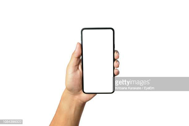 close-up of hand holding smart phone against white background - menschliche hand stock-fotos und bilder