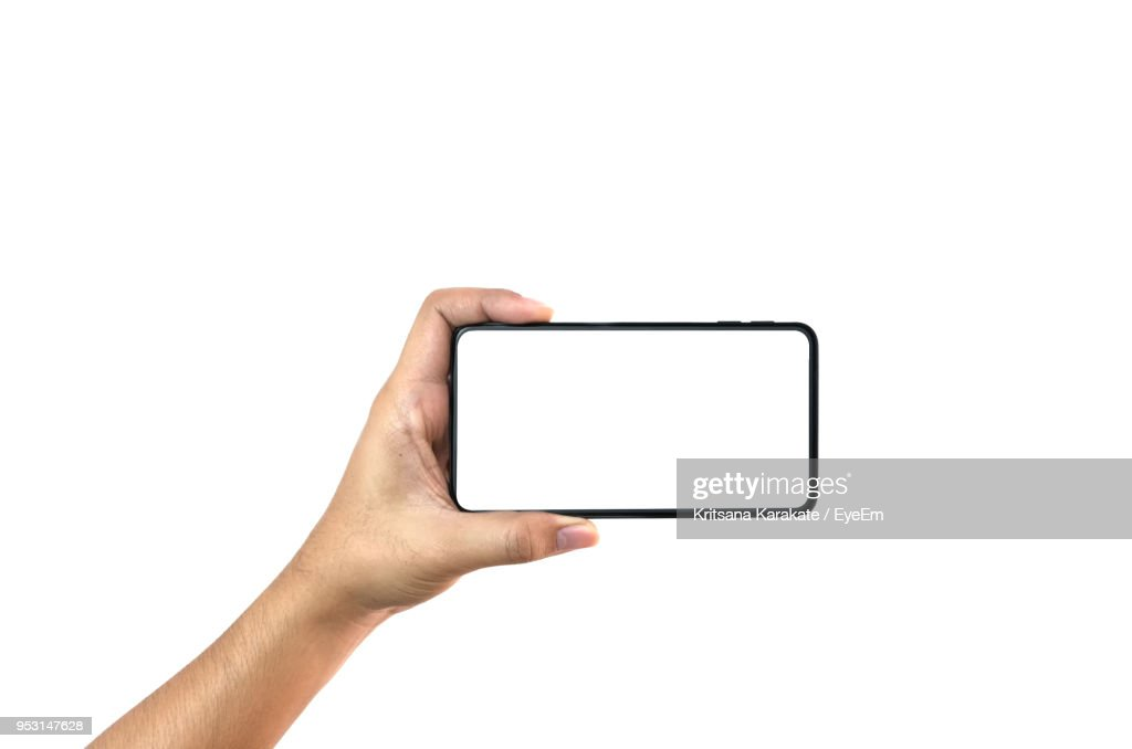 Close-Up Of Hand Holding Smart Phone Against White Background : Stock Photo