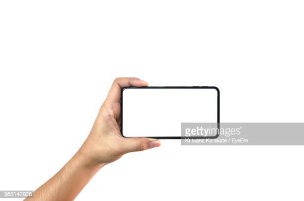 close-up of hand holding smart phone against white background - cogiendo fotografías e imágenes de stock